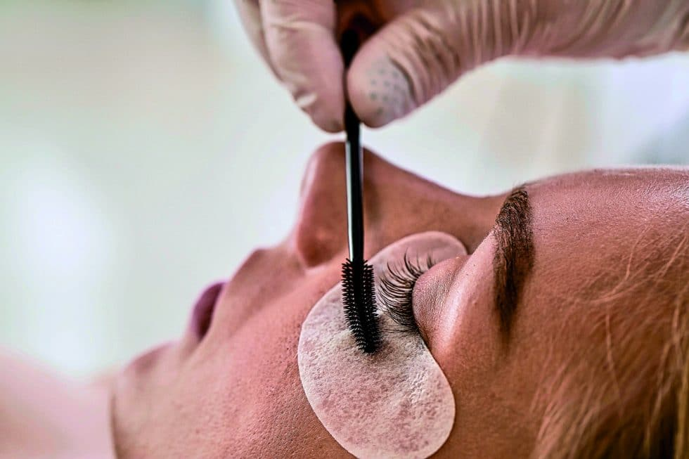 Young woman undergoing procedure of eyelashes lamination in beau